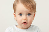 studio portrait of a 12 month old baby boy blond with blue eyes on a white background