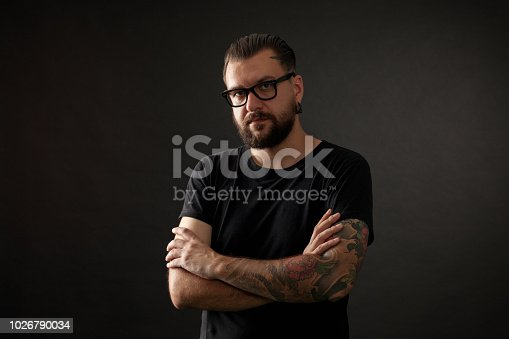 studio portrait of a bearded man wearing glasses on a black background