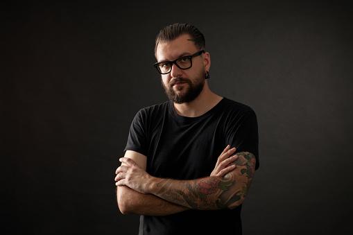 studio portrait of a bearded man wearing glasses on a black background