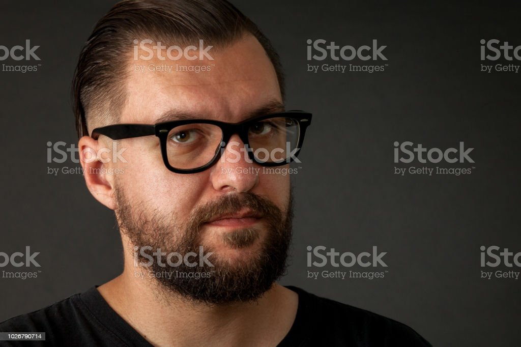 562910619423 Studio portrait of a bearded man wearing glasses on a black background -  Stock image .