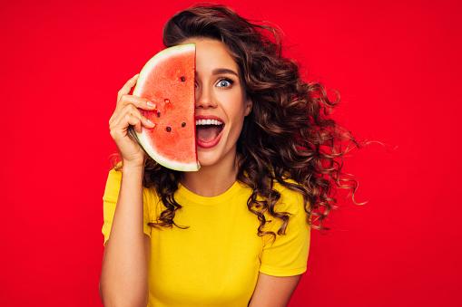 Studio portrait of a beautiful girl with watermelon