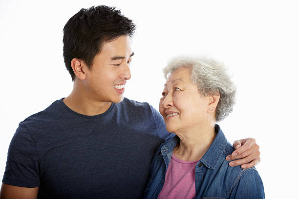 A studio portrait of a Chinese mother and adult son on white Studio Portrait Of Chinese Mother With Adult Son Smiling To Each Other old mother son asian stock pictures, royalty-free photos & images