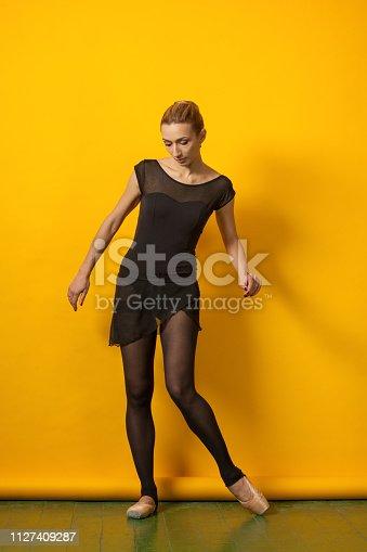 Studio portrait of female ballet dancer on yellow background