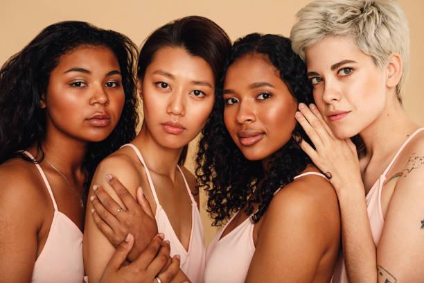 retrato de un estudio de cuatro mujeres mirando a la cámara - sólo mujeres fotografías e imágenes de stock