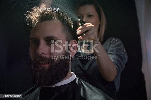 622527180istockphoto Studio portrait of a hairdresser and his client on a black background 1152581382