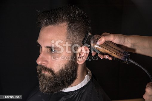 622527180istockphoto Studio portrait of a hairdresser and his client on a black background 1152582337