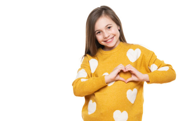 Studioporträt eines kleinen Mädchens auf weißem Hintergrund, das eine Herzgeste mit ihren Händen macht. Förderung eines Kindes, humanitäre Hilfe, Zusammenarbeit, Spenden und Unterstützungskonzept. – Foto