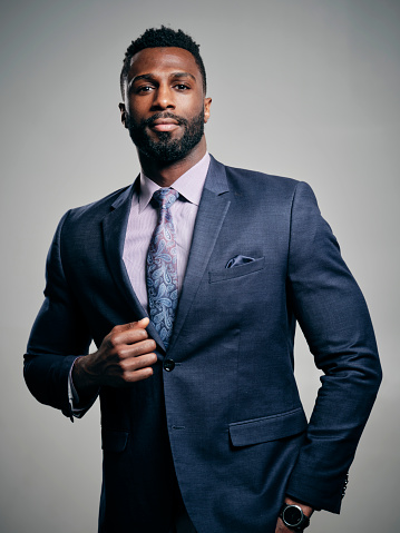 A studio portrait of a handsome black man in a business suit.