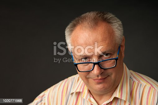 825083248istockphoto studio portrait of a mature man in glasses on a black background 1020771568
