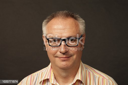 825083248istockphoto studio portrait of a mature man in glasses on a black background 1020771574