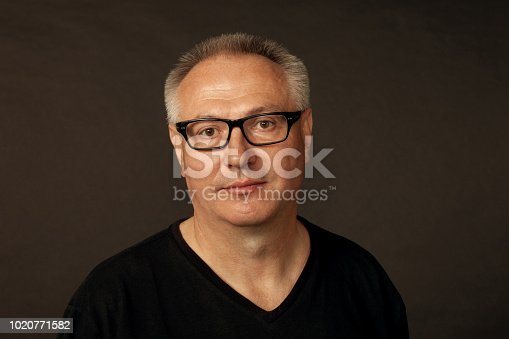 825083248istockphoto studio portrait of a mature man in glasses on a black background 1020771582