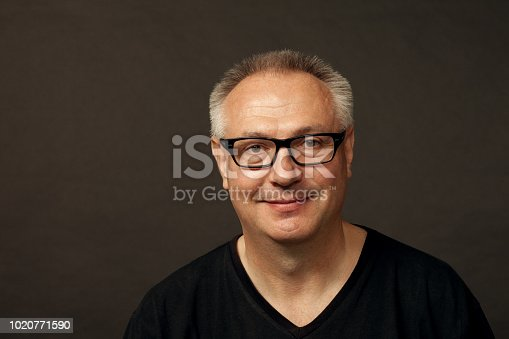 825083248istockphoto studio portrait of a mature man in glasses on a black background 1020771590