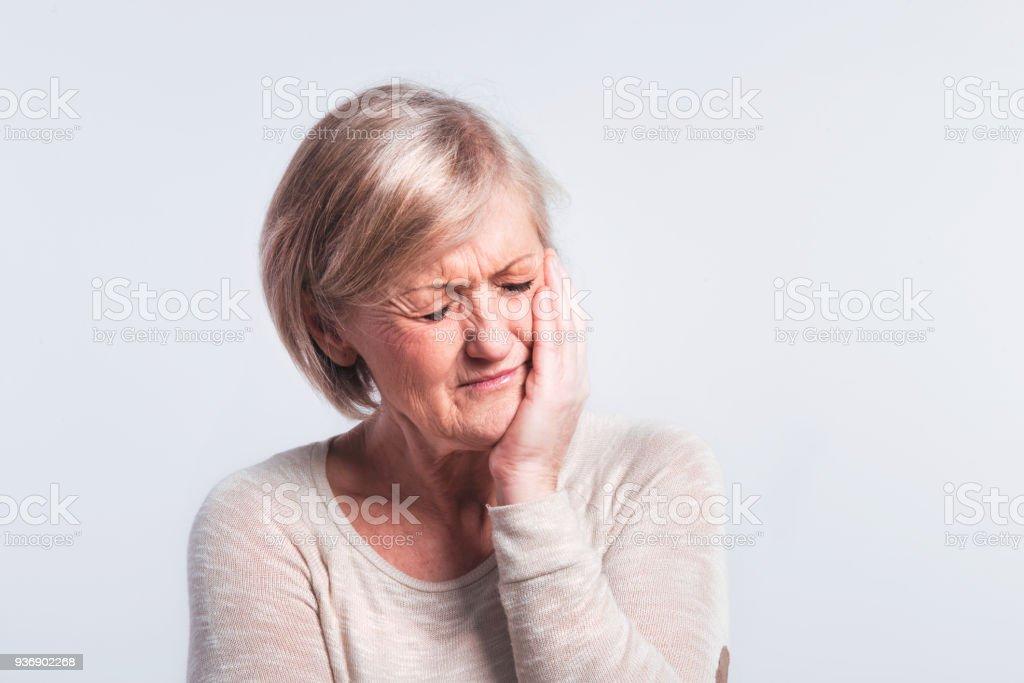Studio-Porträt einer älteren Frau in Schmerzen. – Foto