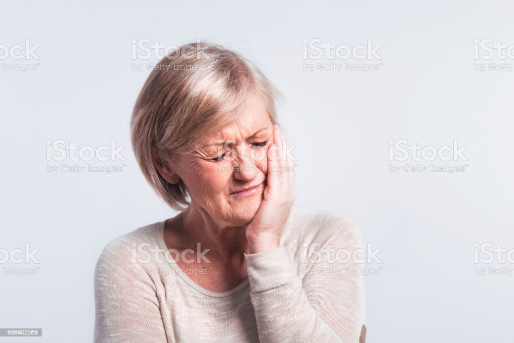 Studio portrait of a senior woman in pain. stock photo