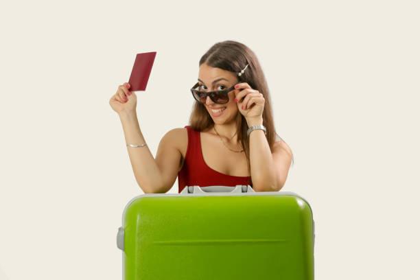 Studioporträt eines jungen Reisenden, der über eine Sonnenbrille schaut, einen Reisepass hält und sich auf einen großen grünen Koffer lehnt, Sommerferienkonzept – Foto