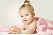 Studio portrait of adorable baby girl playing with plastic rattle toy