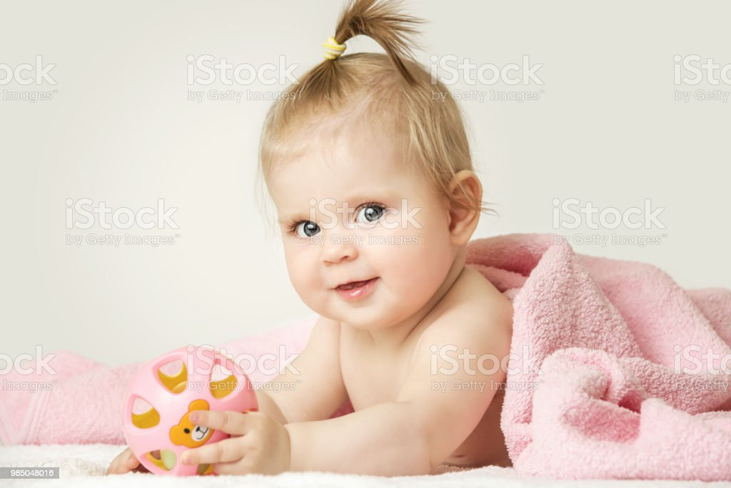 Studio portrait of adorable baby girl playing with plastic rattle toy stock photo