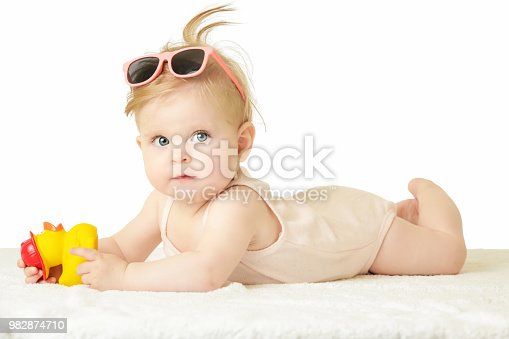 626089510 istock photo Studio portrait of adorable baby girl playing with yellow rubber duck, isolated on the white background, summer vacation concept 982874710