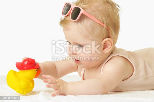 626089510 istock photo Studio portrait of adorable baby girl playing with yellow rubber duck, isolated on the white background, summer vacation concept 982874844