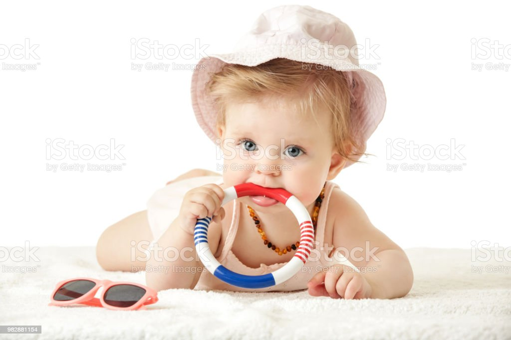 Studio portrait of adorable baby girl wearing pink bucket hat and playing with rattle toy, looking at camera,  isolated on the white background, summer vacation concept stock photo