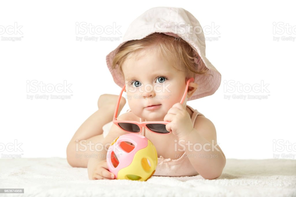 Studio portrait of adorable baby girl wearing pink plastic sunglasses, isolated on the white background, summer vacation concept stock photo