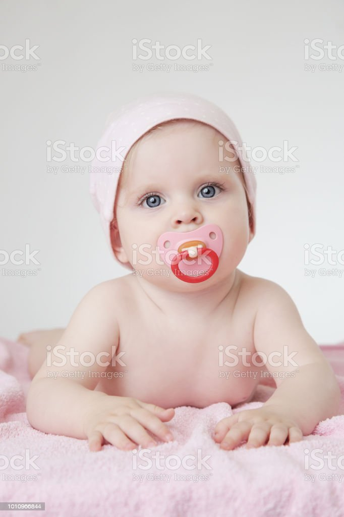 studio portrait of adorable baby girl with pacifier stock photo