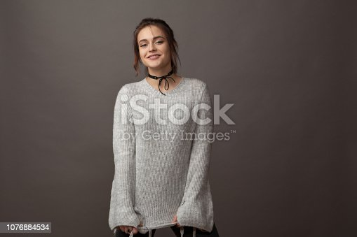 Studio portrait of an attractive 18 year old woman in a gray sweater on a gray background