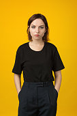 Studio portrait of an attractive 18 year old woman in black pants and a black t-shirt on a yellow background