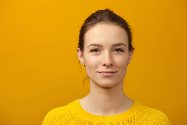 Studio portrait of an attractive 20 year old woman Studio portrait of an attractive 20 year old woman in a yellow sweater on a yellow background belarus stock pictures, royalty-free photos & images