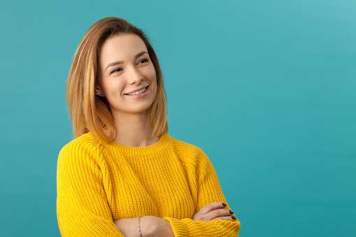 Studio portrait of an attractive 20 year old woman in a yellow sweater on a blue background