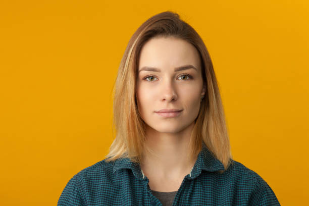 Studio portrait of an attractive 20 year old woman Studio portrait of a 20 year old attractive woman with dyed hair in a blue shirt on a yellow background 20 24 years stock pictures, royalty-free photos & images