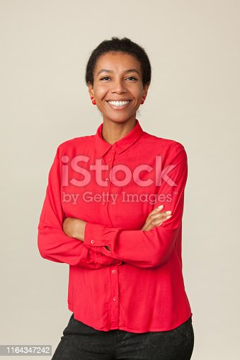 Studio portrait of an attractive 30 year old woman in a red shirt on a beige background