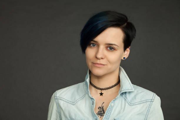 studioporträt einer attraktiven 30-jährigen frau mit blauen haaren im jeanshemd auf schwarzem hintergrund - molekül tattoo stock-fotos und bilder