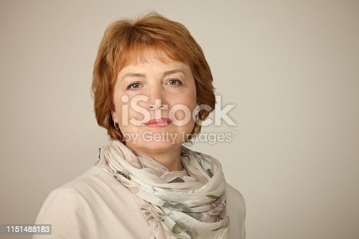Studio portrait of an attractive 60 year old woman on a beige background