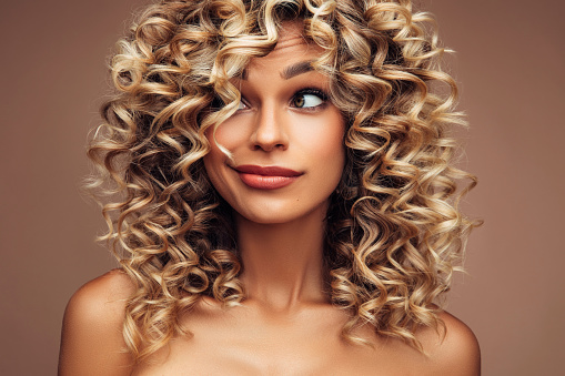 Studio portrait of attractive young woman with voluminous curly hairstyle