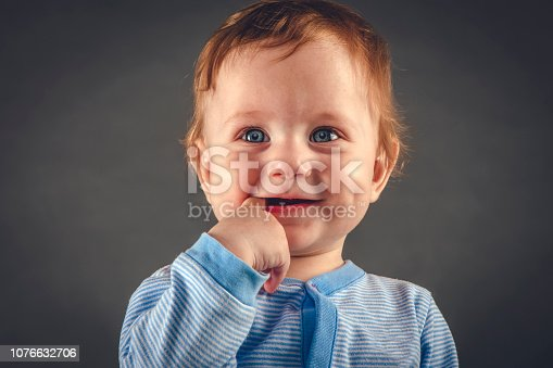 Cute baby boy 9 months old in studio against blue-grey background