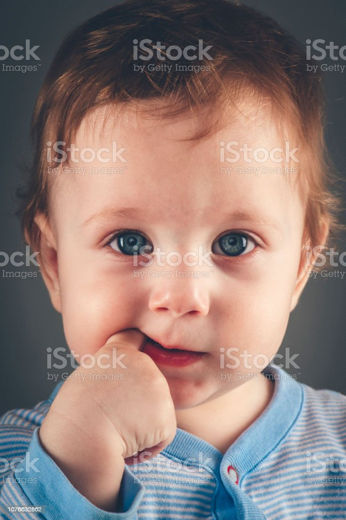 Studio portrait of baby boy aged 9 months on grey-blue background stock photo