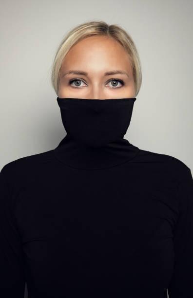 Studio-Porträt der schönen, eleganten Frau, die Gesicht in schwarzem Turtleneck versteckt – Foto