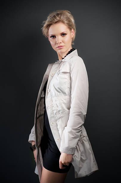 Studio portrait of beautiful woman in black dress and coat stock photo