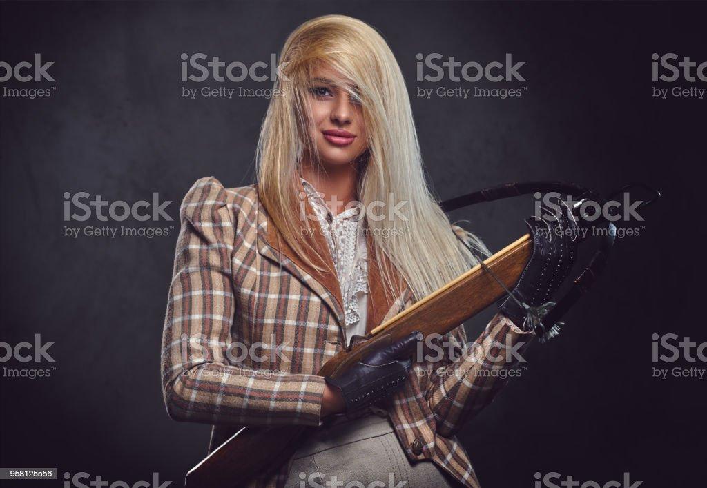 Portrait en studio de blonde femme façonnée est titulaire d'une arbalète. - Photo
