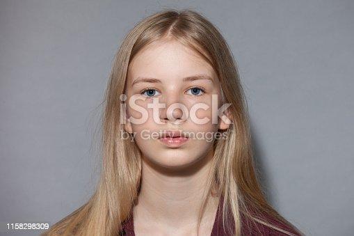 Studio portrait of blonde teen girl on gray background