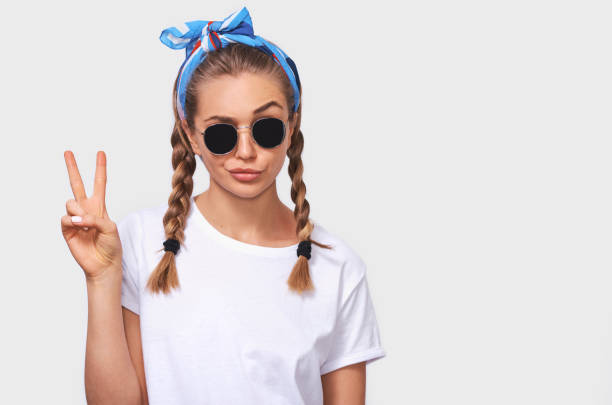 Studio portrait of cheerful blonde young woman wearing trendy sunglasses, white t-shirt and blue headband, making a duck face and showing peace sign. Student girl going crazy with braids hairstyle stock photo