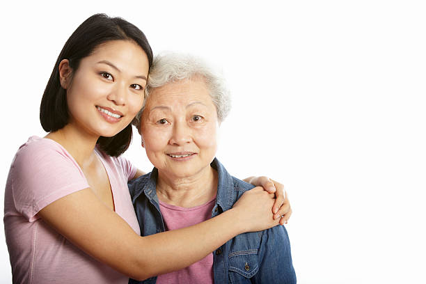 Studio Portrait Of Chinese Mother With Adult Daughter Studio Portrait Of Chinese Mother With Adult Daughter Hugging Each Other Smiling old mother son asian stock pictures, royalty-free photos & images