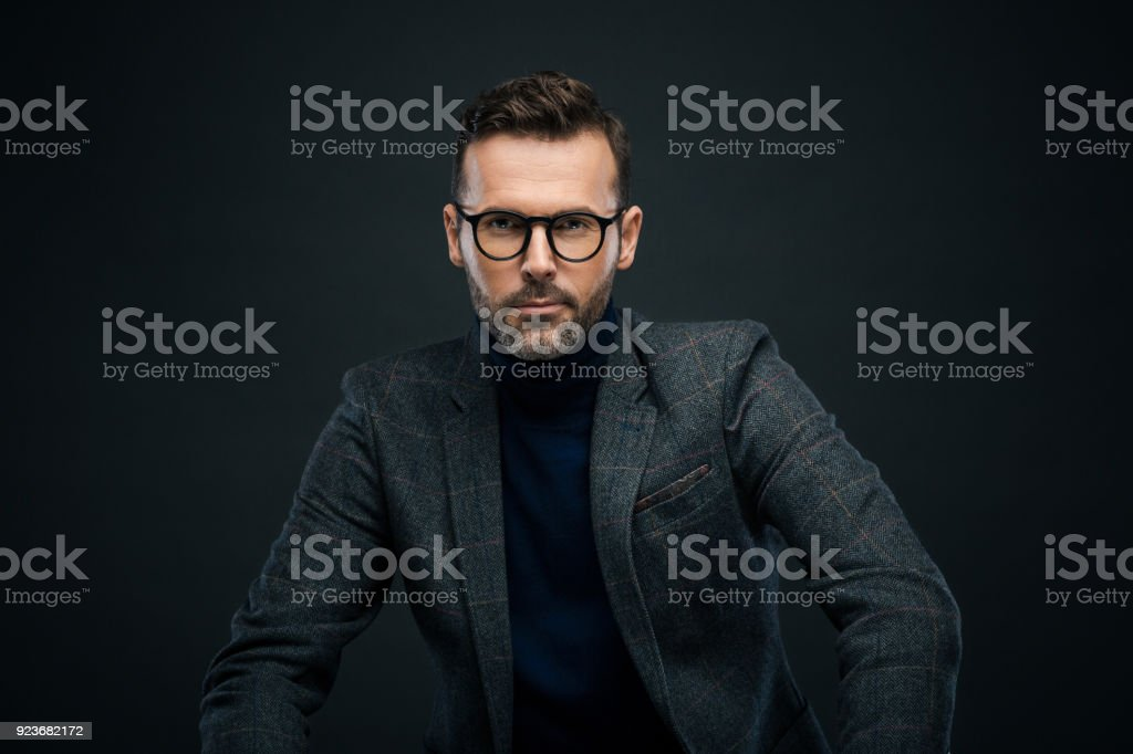 Studio portrait of confident man, dark background Portrait of handsome businessman in tweed jacket and glasses sitting against black background, looking at camera. 30-39 Years Stock Photo