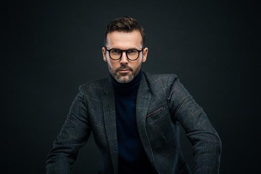 Studio Portrait Of Confident Man Dark Background Stock Photo - Download Image Now