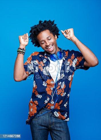 istock Studio portrait of dancing young man in hawaiian shirt 1214667288