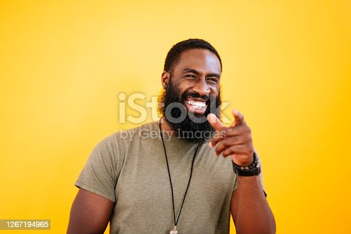 Candid front view of mid adult black man with short hair and full beard in heather t-shirt, smiling and pointing away from camera against yellow background.