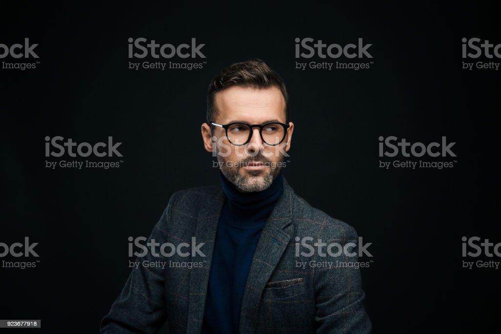 Studio portrait of elegant, charming man, dark background Portrait of handsome businessman in tweed jacket and glasses against black background, looking away. 30-39 Years Stock Photo