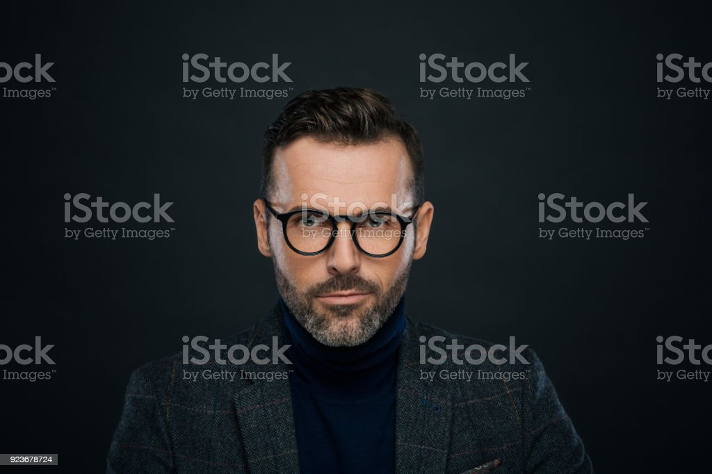 Studio portrait of elegant, charming man, dark background Portrait of handsome businessman in tweed jacket and glasses against black background, looking at camera. 30-39 Years Stock Photo