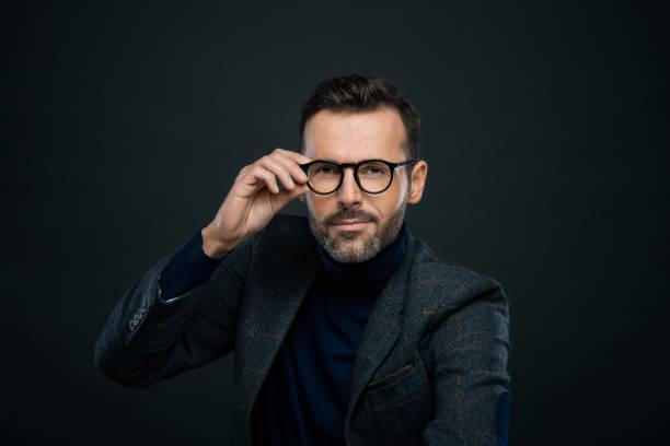 studio portrait of elegant handsome man, dark background - eyewear stock pictures, royalty-free photos & images